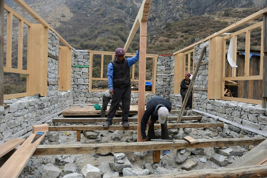 Nepalese workers rebuild a tea house in Langtang valley in Nepal's Rasuwa district on April 7, 2016.