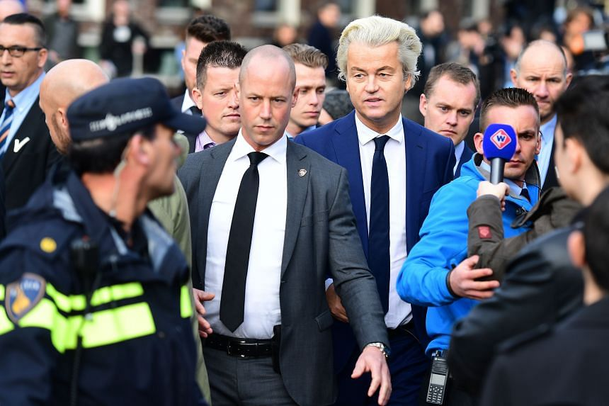Netherlands' politician Geert Wilders (in blue suit) of the Freedom Party leaving a polling station after casting his ballot on March 15, 2017, in The Hague.