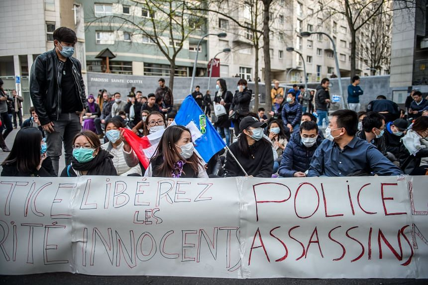 Members of the French chinese community gathering outside a police station behind a banner reading 'Police Assassins', to protest against police violence in Paris, France, on 28 March 2017.