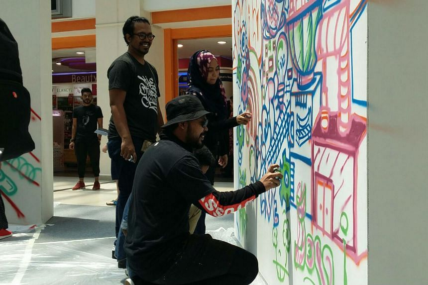 As part of the #BeyondIT campaign leading up to the Funan's closure on July 1, Singapore graffiti artist Ceno2 (foreground, with hat) leads a group of graffiti art workshop participants to brainstorm ideas for the future mall.