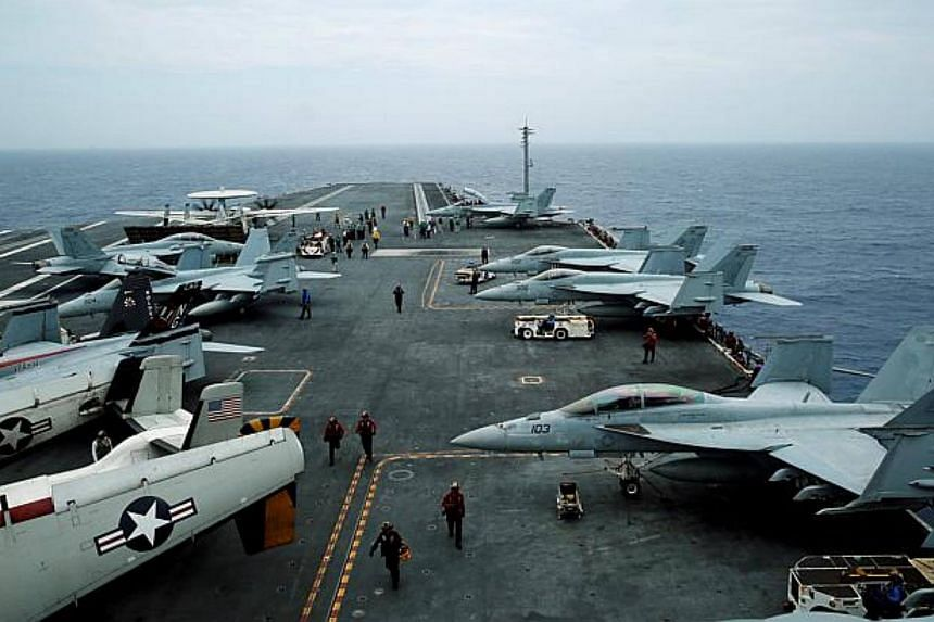 Hornet fighter jets and an E-2D Hawkeye plane are seen on the US aircraft carrier John C. Stennis during the Malabar joint military exercise in 2016.