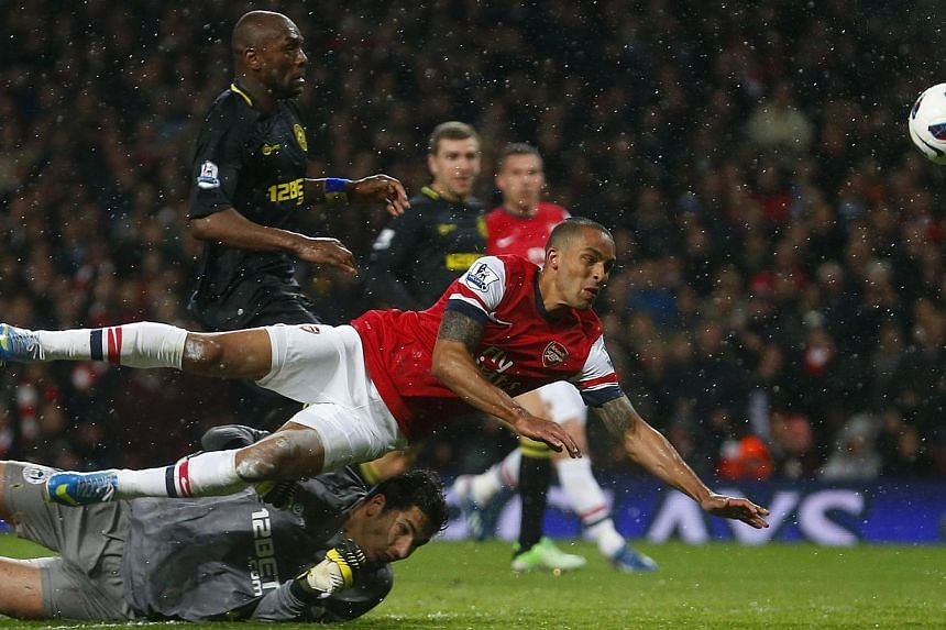 Theo Walcott of Arsenal scores against Wigan Athletic during their English Premier League soccer match at the Emirates Stadium in London, on May 14, 2013. Singapore football fans are fuming over yet another service breakdown by SingTel's mioTV during