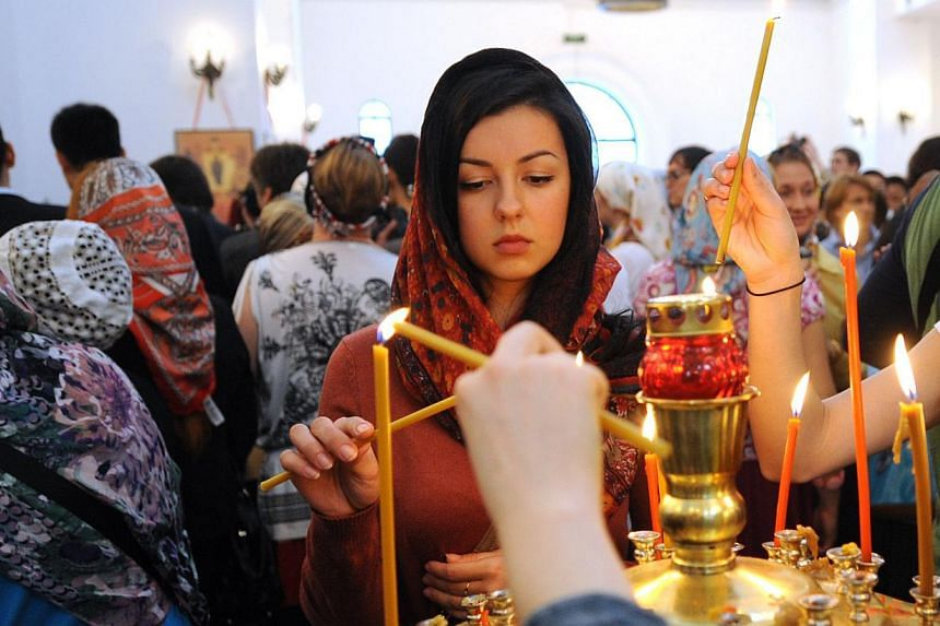 Worshippers light candles during a service in the historic Russian Orthodox church in Shanghai, on Wednesday, May 15, 2013. The head of the Russian Orthodox Church held a service in a historic Shanghai church on Wednesday, its first in more than half