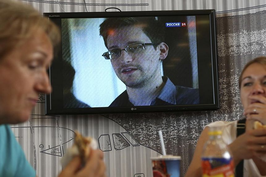 Transit passengers eat at a cafe with a TV screen with a news programme showing a report on Edward Snowden, in the background, at Sheremetyevo airport in Moscow, Russia on June 26, 2013.US intelligence leaker Edward Snowden, who has been holed