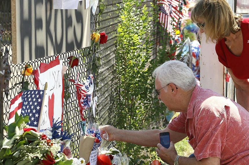 People look at mementos at a memorial dedicated to the 19 firefighters killed in the nearby wildfire in Prescott, Arizona, on July 2, 2013.Thousands of mourners, including United States (US) Vice-President Joe Biden, paid tribute on Tuesday to
