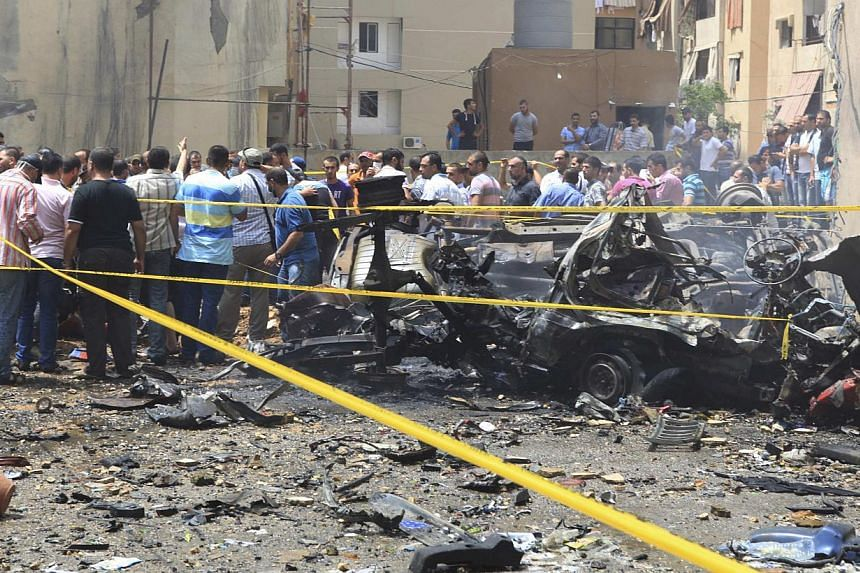 Security personnel and people gather at the site of an explosion in Beirut's southern suburbs, on July 9, 2013.A car bomb exploded on Tuesday in a Beirut stronghold district of the Lebanese Hezbollah militant group that has been fighting in Syria's c