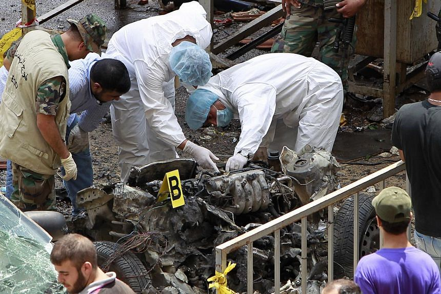 Forensic experts inspect the remnants of a car bomb at the scene of a bombing in the Beir el-Abed, a southern suburb of Beirut, Lebanon, on Tuesday, July 9, 2013. A large explosion rocked a stronghold of the Shiite militant Hezbollah group south of t