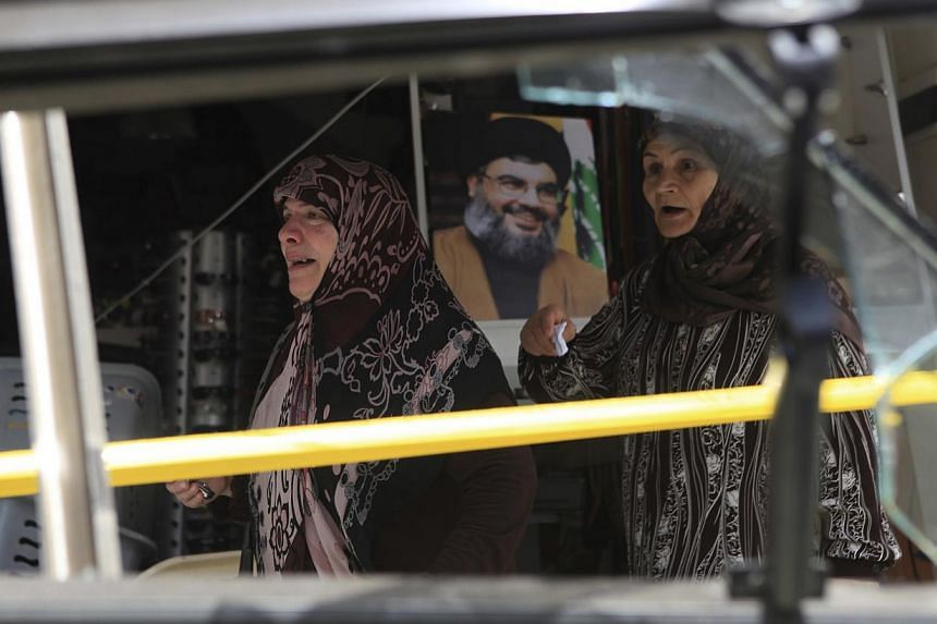Women react as they walk past a picture of Lebanon's Hezbollah leader Sayyed Hassan Nasrallah, as seen from a shattered window near the site of an explosion in Beirut's southern suburbs, on July 9, 2013. A car bomb exploded on Tuesday in a Beirut str