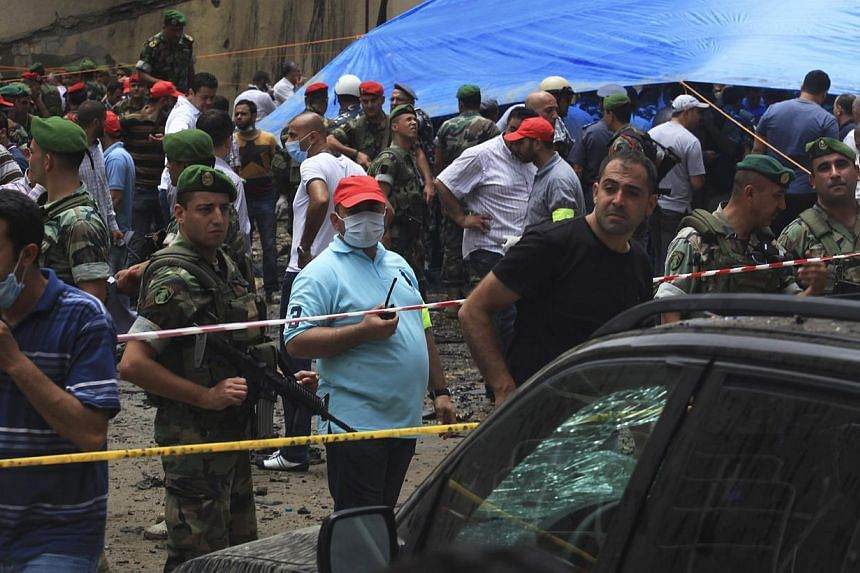 Lebanese army soldiers, security forces and Hezbollah members gather at the site of an explosion in Beirut's southern suburbs, on July 9, 2013. A car bomb exploded on Tuesday in a Beirut stronghold district of the Lebanese Hezbollah militant group th