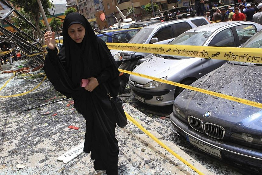A woman walks over shattered glass, past damaged cars near the site of an explosion in Beirut's southern suburbs, on July 9, 2013. A car bomb exploded on Tuesday in a Beirut stronghold district of the Lebanese Hezbollah militant group that has been f