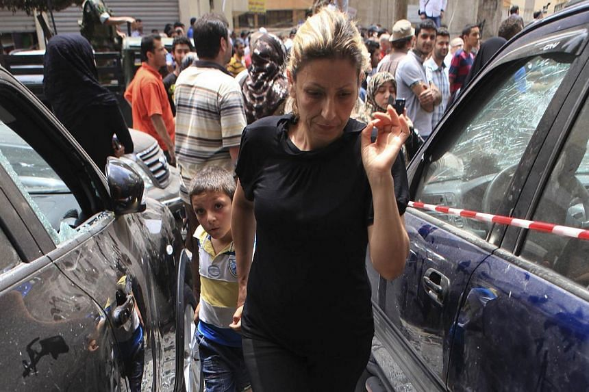 A woman holding a boy, walks over shattered glass, between damaged cars near the site of an explosion in Beirut's southern suburbs, on July 9, 2013. A car bomb exploded on Tuesday in a Beirut stronghold district of the Lebanese Hezbollah militant gro