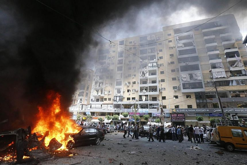 Firefighters and residents gather at the site of an explosion in Beirut's southern suburb neighbourhood of Bir al-Abed on July 9, 2013. A car bomb rocked Beirut's southern suburbs, stronghold of Lebanon's Shiite Hezbollah movement, wounding 15 people