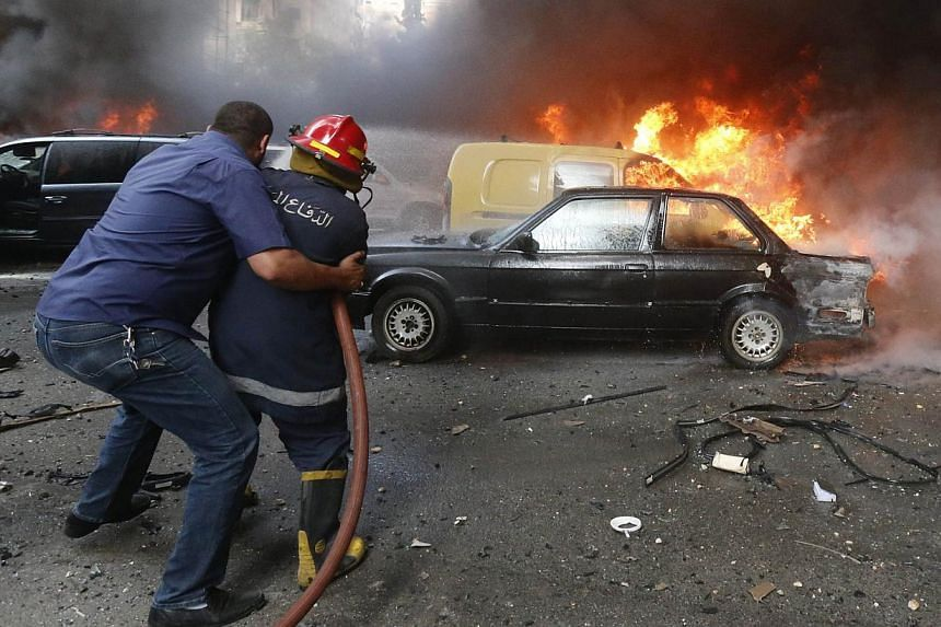 A firefighter is helped as he extinguishes fire at the site of an explosion in Beirut's southern suburb neighbourhood of Bir al-Abed on July 9, 2013. A car bomb rocked Beirut's southern suburbs, stronghold of Lebanon's Shiite Hezbollah movement, woun