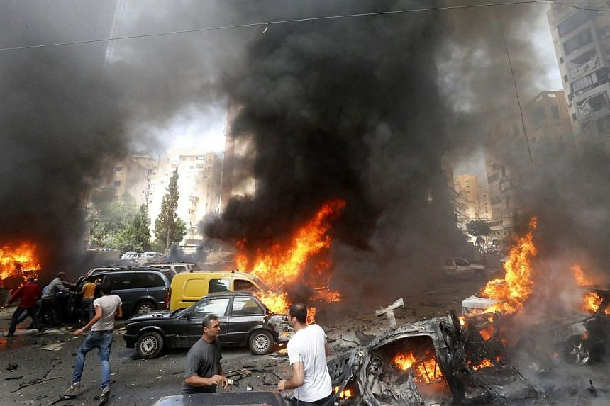 Civilians gather at the of an explosion in Beirut's southern suburb neighbourhood of Bir al-Abed on July 9, 2013. A car bomb rocked Beirut's southern suburbs, stronghold of Lebanon's Shiite Hezbollah movement, wounding 15 people, television reports a