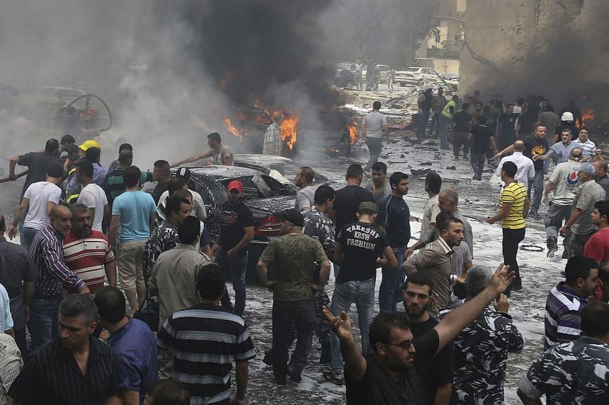 Civil Defence workers, Hezbollah members, policemen and civilians gather at the site of an explosion in Beirut's southern suburbs, on July 9, 2013. At least 18 people were wounded by a car bomb blast in Beirut's southern suburbs on Tuesday, a strongh