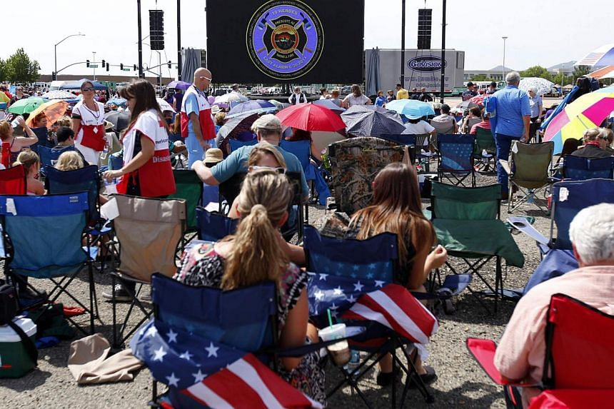The crowd watches large TV screens as people sit outside a memorial for the fallen members of Prescott Fire Department's Granite Mountain Hotshots team in Prescott Valley, Arizona, on July 9, 2013. Thousands of mourners, including United States (US)
