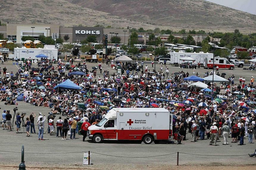 People watch a memorial service for the fallen members of the Granite Mountain Hotshots on a big screen outside the memorial arena, in Prescott Valley, Arizona, on July 9, 2013. Thousands of mourners, including United States (US) Vice-President Joe B