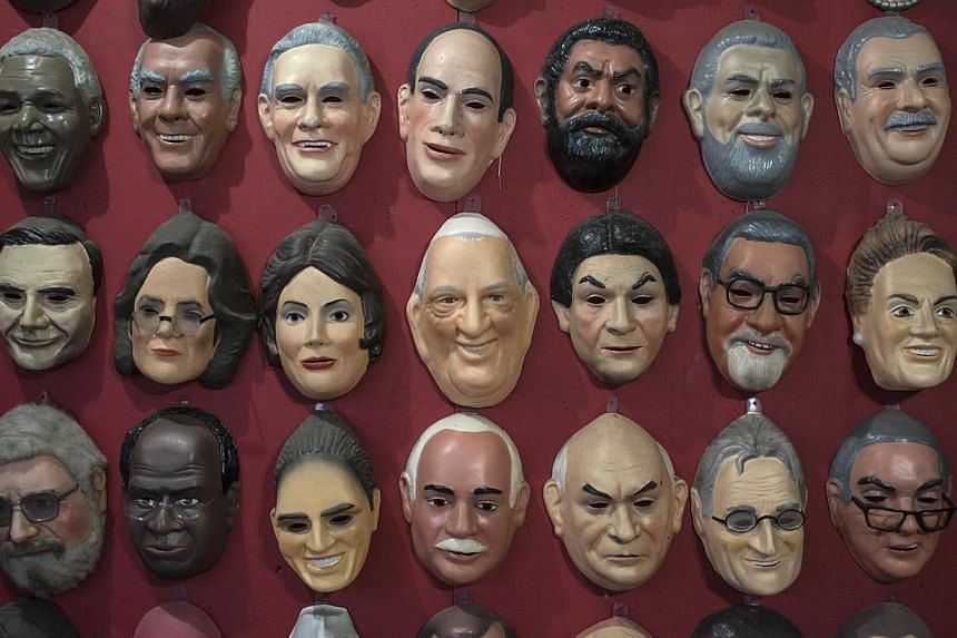 A mask in the likeness of Pope Francis (centre), hangs alongside masks of other personalities in the offices of the Condal mask-making factory in Sao Goncalo near Rio de Janeiro, Brazil, on Tuesday, July 9, 2013. Some 1.5 million pilgrims are expecte