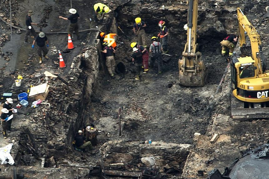 Workers comb through the debris after a train derailed causing explosions of railway cars carrying crude oil on July 9, 2013, in Lac-Megantic, Quebec, Canada. Investigators sifted through the charred remains of Lac-Megantic's historic downtown early