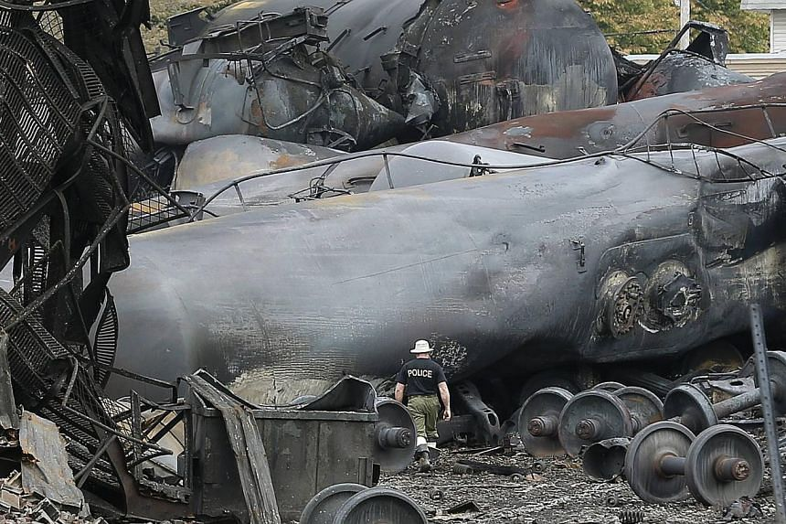 A police officer walks amongst axle gear in Lac Megantic, July 9, 2013. Transport Canada said on Tuesday the Montreal, Maine & Atlantic Railway train that derailed on the weekend in Lac-Megantic, Quebec, leaving 50 people dead or missing, had bee
