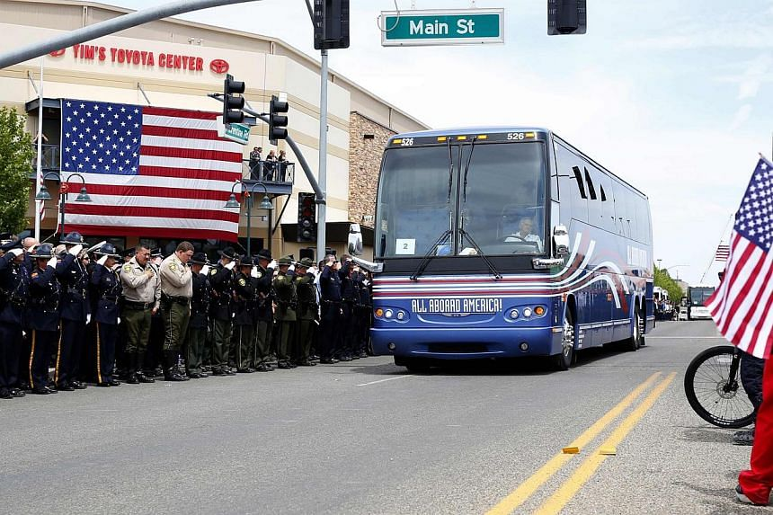 People salute as a bus full of family members leaves a memorial for the Prescott Fire Department's Granite Mountain Hotshots team in Prescott Valley, Arizona, on July 9, 2013.Thousands of mourners, including United States (US) Vice-President Joe Bide