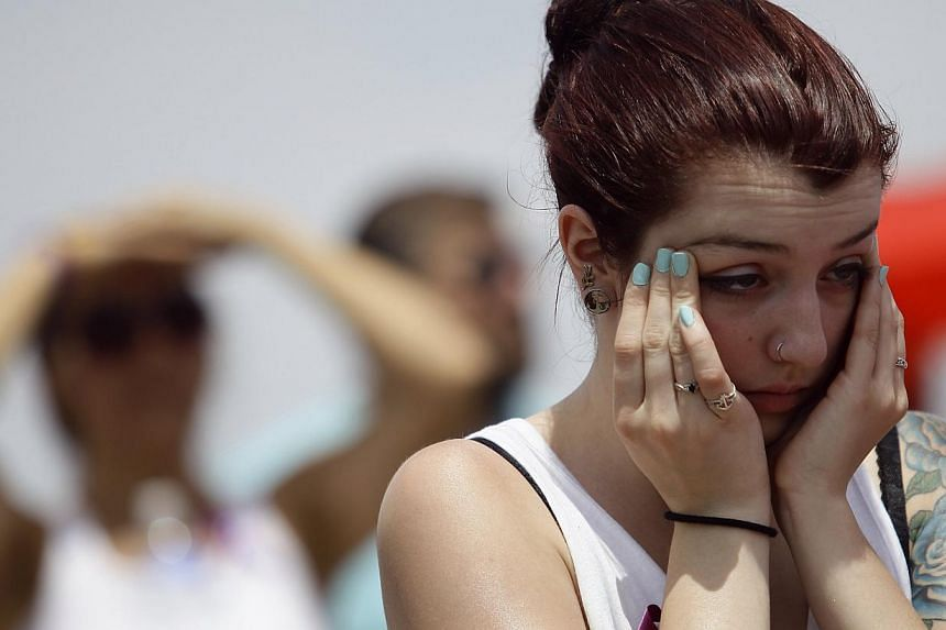 A woman holds her hands to her face as she attends a memorial for the Prescott Fire Department's Granite Mountain Interagency Hot Shot Crew in Prescott Valley, Arizona, on July 9, 2013. Thousands of mourners, including United States (US) Vice-Preside