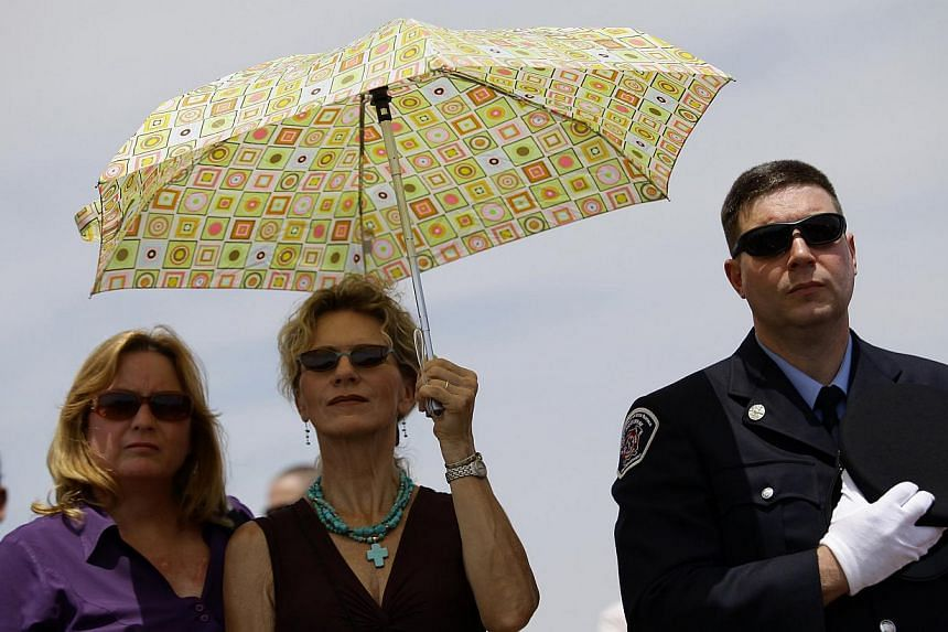 A firefighter (right) holds his hat over his heart as he attends a memorial for the Prescott Fire Department's Granite Mountain Interagency Hot Shot Crew in Prescott Valley, Arizona, on July 9, 2013. Thousands of mourners, including United States (US