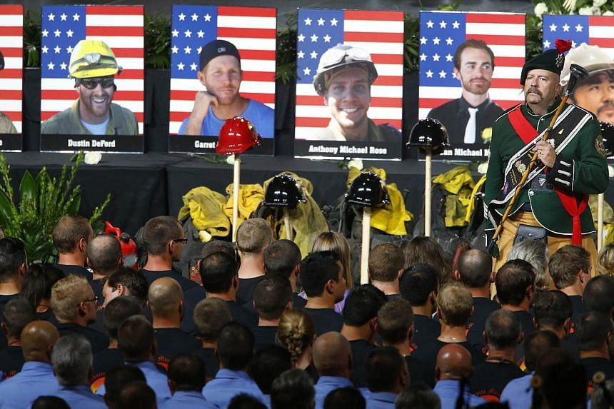 Drum Major Brian Brendel of the Prescott Memorial Pipe and Drums leads the massed band during a memorial service at Tim's Toyota Center in Prescott Valley, Arizona, on July 9, 2013, for the 19 Granite Mountain hotshot firefighters that were killed on