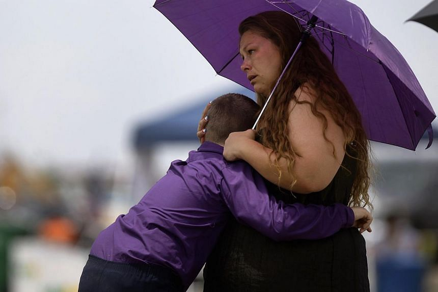 A woman hugs a boy during a memorial for the members of the Prescott Fire Department's Granite Mountain Hotshots in Prescott Valley, Arizona, on July 9, 2013. Thousands of mourners, including United States (US) Vice-President Joe Biden, paid tribute
