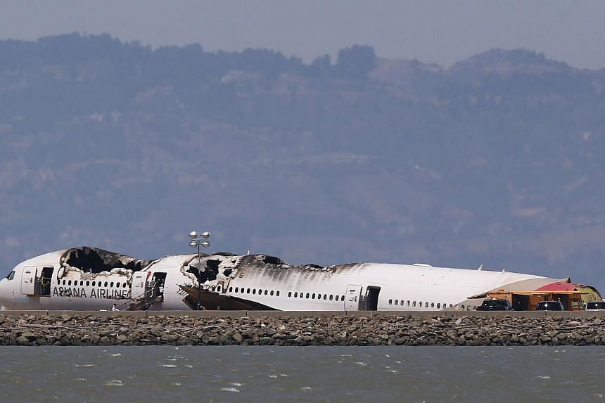 The charred remains of the Asiana Airlines flight 214 sits on the runway at San Francisco International Airport in San Francisco, California, on July 9, 2013. The flight crew of the Asiana Airlines Boeing 777 which crash landed at San Francisco
