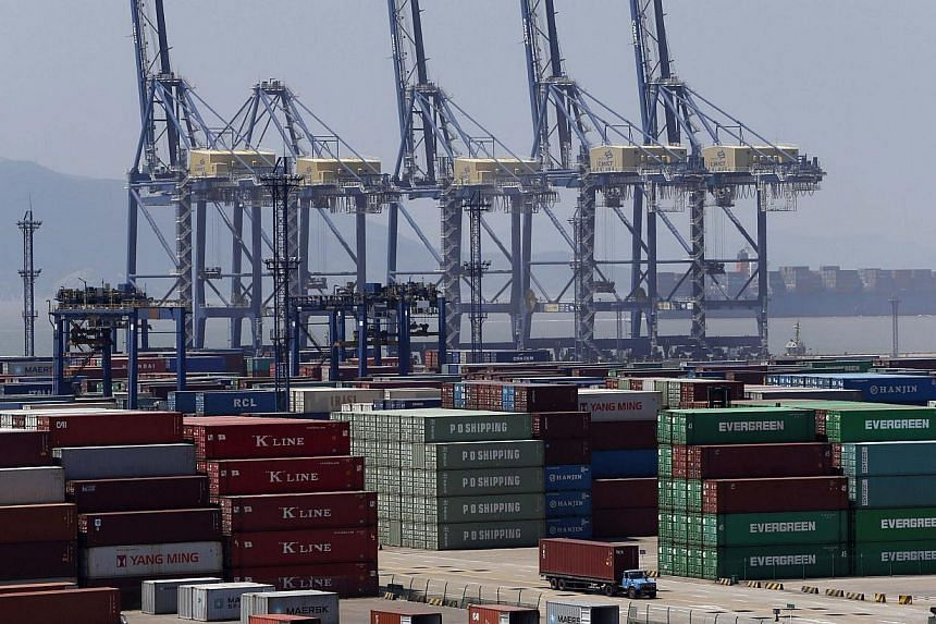 A truck drives past shipping containers at a port in Ningbo, Zhejiang province in China, on July 9, 2013. China's exports fell 3.1 per cent in June from a year earlier, the first decline since January 2012, while imports dropped 0.7 per cent, severel