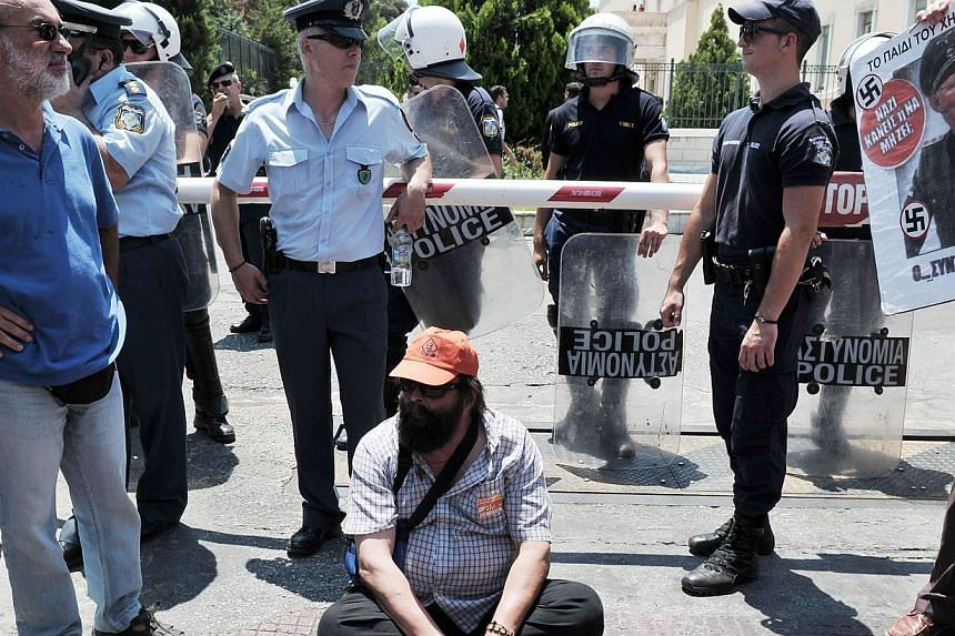 A municipal employee sits in front of the Greek parliament in Athens, during their protest rally on July 9, 2013. Greece's main unions on Wednesday, July 10, 2013, said they would hold a general strike on July 16 to oppose a new round of civil servic