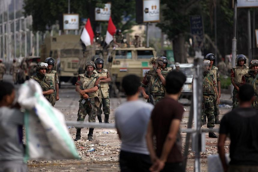 """Supporters of ousted President Mohammed Mursi protest as army soldiers guard at the Republican Guard building in Nasr City, Cairo, Egypt on July 9, 2013. Amnesty International said on Wednesday, July 10, 2013, it had evidence pointing to the """"disprop"""