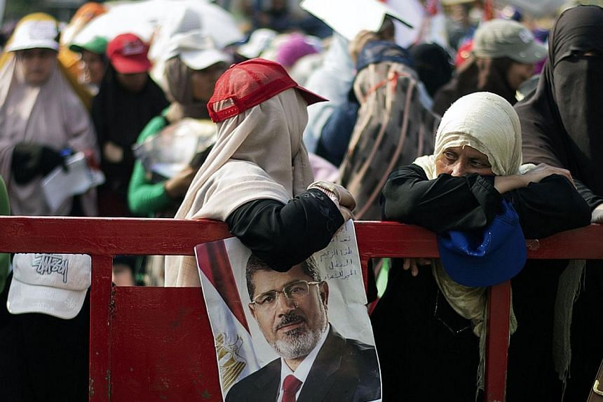 An Egyptian woman lean on a barrier as thousands of Muslim Brotherhood members and supporters of ousted President Mohamed Mursi gather in front of Rabaa al-Adawiya mosque on July 9, 2013, in Cairo. Egypt's main liberal alliance withdrew a statement t