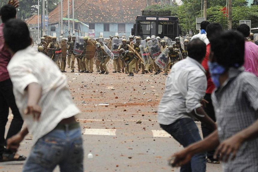 Supporters from the Students Federation of India (SFI) throw pieces of bricks towards the police during a protest near a university in the southern Indian state of Kerala on July 9, 2013. The protest called for the resignation of the state's chief mi