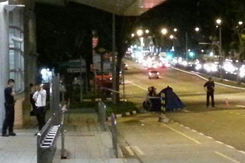 Police stand beside a tent covering a body found outside Kovan MRT. The police have classified the case of the two bodies found within 1 km of each other at Kovan as suspected murder. -- ST PHOTO: DAVID EE