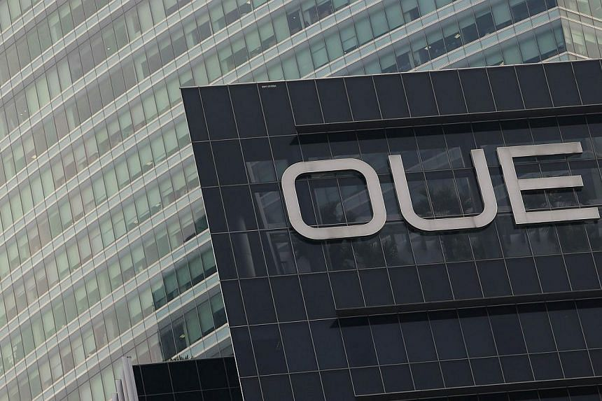The Overseas Union Enterprise (OUE) logo is seen on its office building in Singapore. OUE is seeking to raise up to $391 million by spinning off two properties into a trust. -- FILE PHOTO: REUTERS