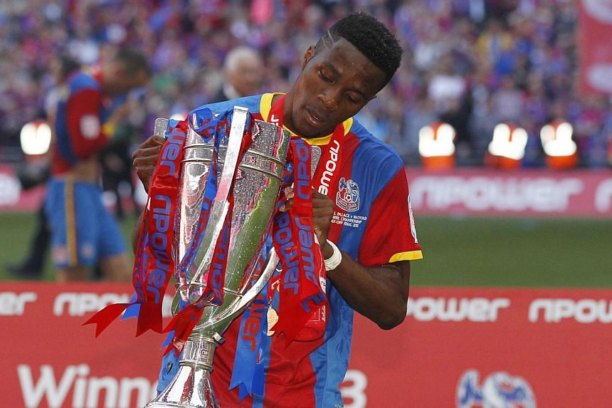 Crystal Palace's English striker Wilfried Zaha (above) poses with the trophy following victory in the English Championship Play Off final football match between Crystal Palace and Watford at Wembley Stadium in London on May 27, 2013. Manchester Unite