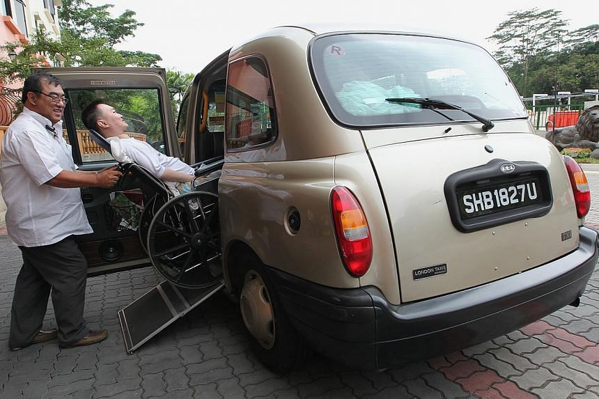 London Taxi cabby Tan Seoh Bung, 58, helping Eddie Leow (on wheelchair), 40, to get onboard his London Taxi. Transport operator SMRT has put its final batch of 15 London cabs on the road on Thursday, doubling its fleet of vehicles that wheelchair use