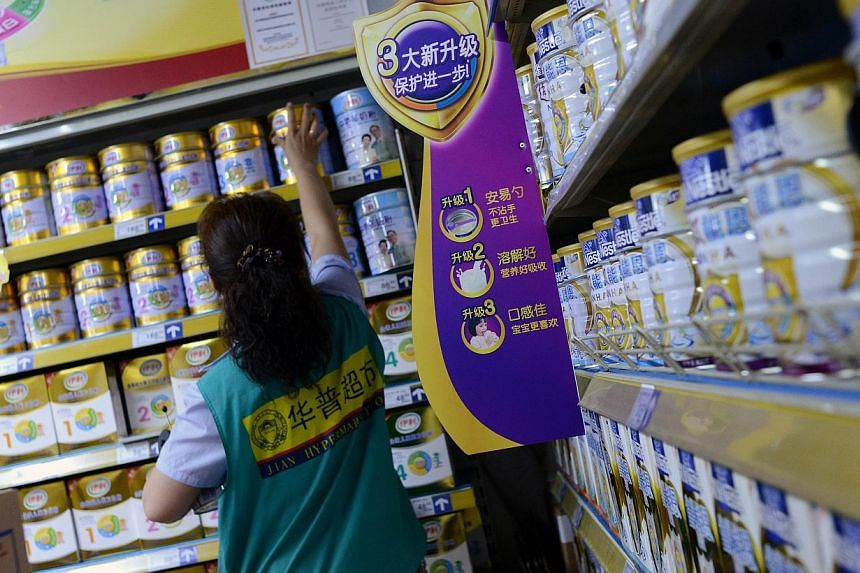 A saleswoman checks items for sale next to a shelf of milk powder at a supermarket in Beijing on July 4, 2013. Mead Johnson Nutrition Co said on Wednesday it will cut the price of its infant milk formula in China, becoming the latest company to