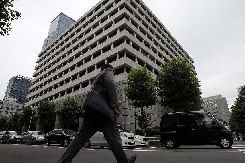 A man walks past the Bank of Japan headquarters in Tokyo on July 5, 2013. The Bank of Japan is set to keep policy steady on Thursday and upgrade its view of the economy on expectations that a weak yen and its massive monetary stimulus already in plac