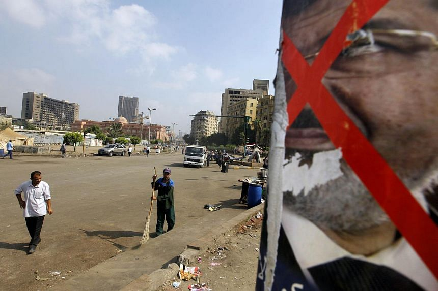 An Egyptian walks past a poster of ousted President Mohammed Morsi in Tahrir Square in Cairo, Egypt, on Monday, July 8, 2013. Seven days after the Egyptian military deposed the democratically elected president Mohamed Mursi, the United States ha