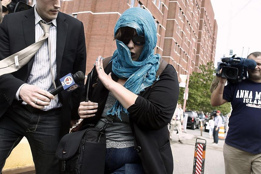 "A supporter of Boston Marathon bombing suspect Dzhokhar Tsarnaev leaves federal court after his arraignment on July 10, 2013, in Boston. Wearing an orange prison jumpsuit, with his arm in a cast, Tsarnaev pleaded ""not guilty"" to committing the w"
