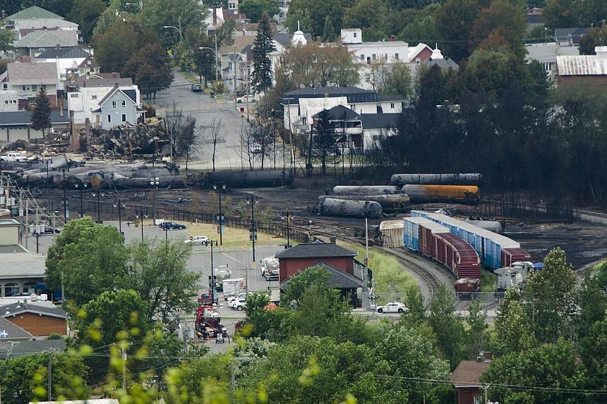 "Scorched oil tankers remain on July 10, 2013, at the train derailment site in Lac-Megantic, Quebec. The head of the company whose oil-tanker train exploded and devastated a small Quebec town faced cries of ""murderer"" from furious town residents"