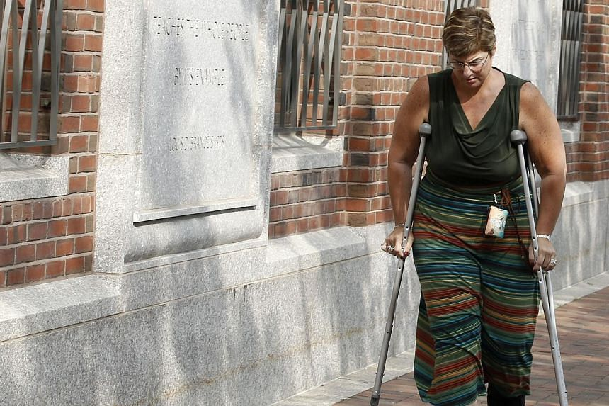 """Boston Marathon bombing victim Karen Brassard leaves federal courthouse following the arraignment of bombing suspect Dzhokhar Tsarnaev on July 10, 2013, in Boston.Wearing an orange prison jumpsuit, with his arm in a cast, Tsarnaev pleaded """"not"""