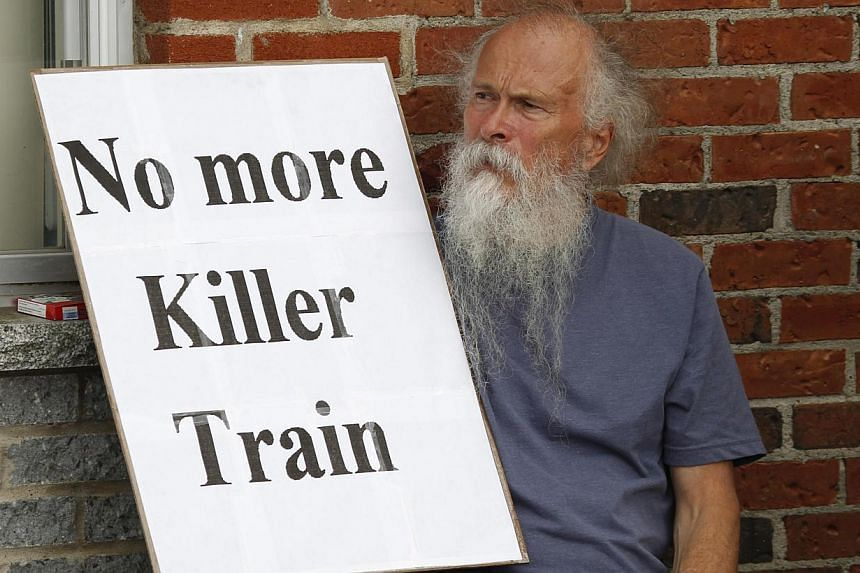 "A man sits with a sign outside the school sheltering evacuees in Lac-Megantic, Quebec, on July 10, 2013. The head of the company whose oil-tanker train exploded and devastated a small Quebec town faced cries of ""murderer"" from furious town resid"