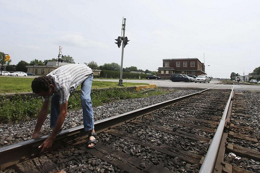 A resident demonstrates the condition of the rail line from Montreal, Maine and Atlantic Railways (MMA), which passes through the town of Farnham, Quebec, on July 10, 2013. The head of the company whose oil-tanker train exploded and devastated a