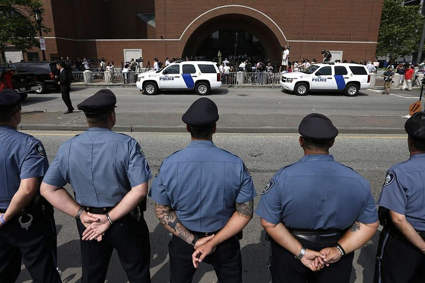 Massachusetts Institute of Technology police officers form a line in front of the federal courthouse in Boston prior to the arraignment of Boston Marathon bombing suspect Dzhokhar Tsarnaev on July 10, 2013. Wearing an orange prison jumpsuit, with his