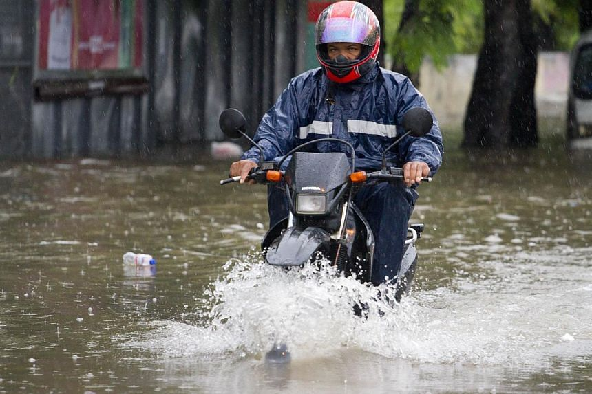 A local resident drives a bike in a flooded street caused by tropical storm Chantal in Santo Domingo on July 10, 2013. Haiti on Wednesday issued a red alert in advance of the arrival of Tropical Storm Chantal, which was due to lash the impoverished C
