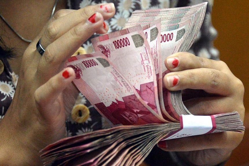 An employee counts Indonesian Rupiah at a money change outlet in Jakarta on June 14, 2013. Indonesia's central bank on Thursday, July 11, 2013, hiked its key interest rate for a second straight month as it seeks to keep inflation in check after a hug